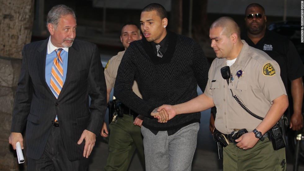 Brown, center, and his attorney Mark Geragos, left, enter the courthouse for Brown's probation progress hearing in Los Angeles on January 28, 2011.