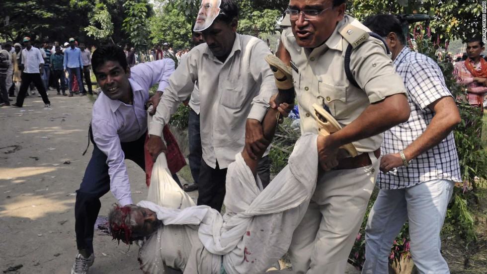 An Indian police officer and bystanders help an injured man when a series of bombs went off before a political rally.