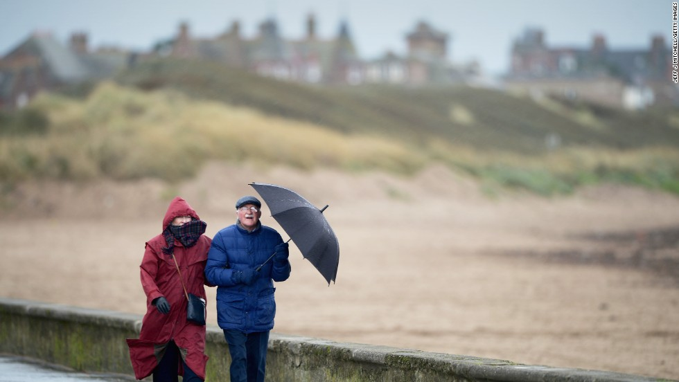 People walk along the Troon South beach in Troon, Scotland, on Monday.