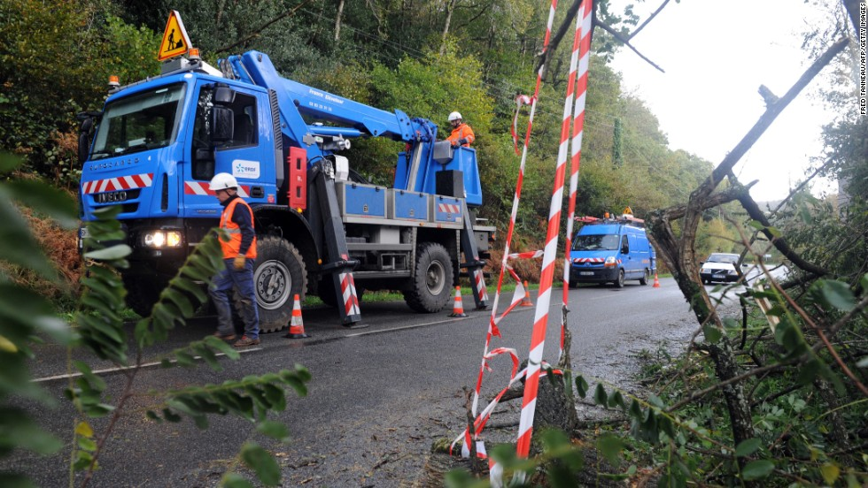 Electric company workers cut tree branches and repair power lines Monday in La Roche-Maurice, France. Officials said early Monday that 42,000 homes in northern France were without electricity.