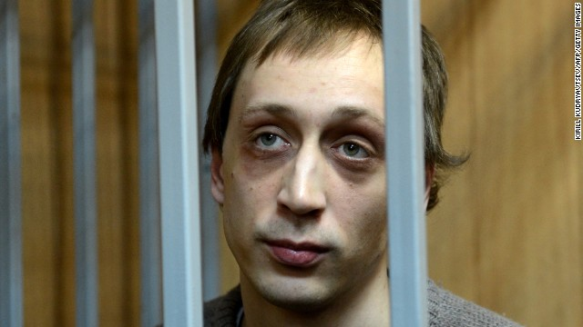 Pavel Dmitrichenko, a leading dancer at Russias Bolshoi Theatre, looks on as he stands inside the defendant's cage during a court hearing in Moscow, on October 22, 2013.