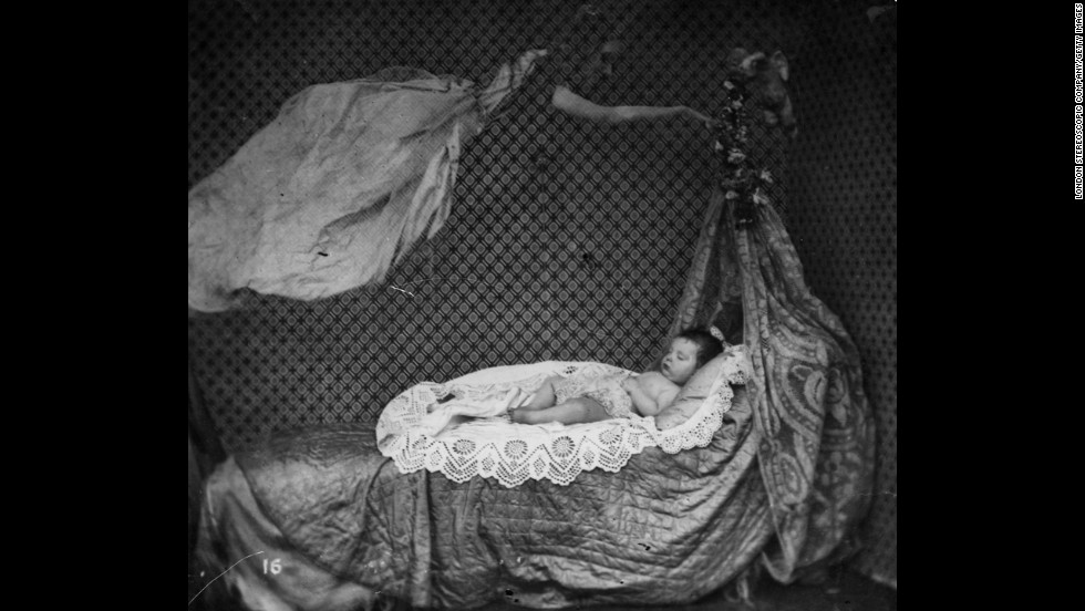 A spectral figure hovers over a sleeping baby in a crib.