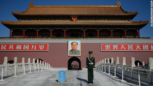 A paramilitary policeman stands before a portrait of Mao Zedong at Tiananmen Gate  in Beijing.