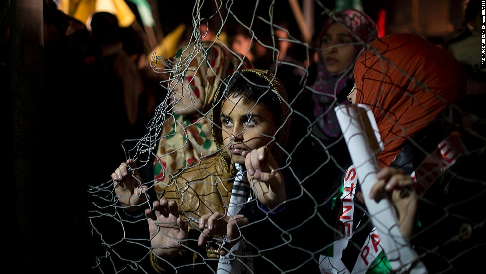 "OCTOBER 30 - GAZA: Palestinian prisoners' relatives wait behind a fence for their release at the Erez Crossing in northern Gaza on October 29. Israel freed 26 veteran prisoners early on October 30 as part of a <a href=""http://cnn.com/2013/10/29/world/meast/israel-palestinian-prisoner-release/index.html?hpt=hp_t3"">deal put together by the U.S. to jump-start stalled Israeli-Palestinian peace talks.</a>"