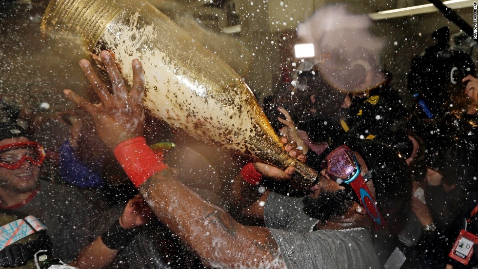 Boston Red Sox's David Ortiz drinks out of a giant bottle of Champagne as he celebrates with teammates. Ortiz was named the series MVP.