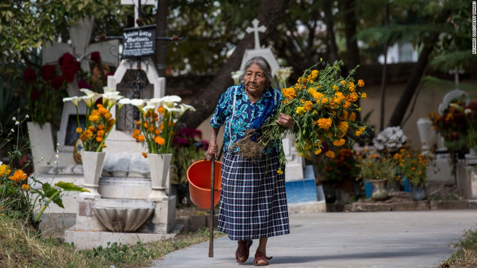 "An elderly Zapotec indigenous woman carries flowers to the grave of a family member at the start of the Day of the Dead festival in Teotitlan, Mexico. ""Marigold flowers are used for Day of the Dead because of their pungent smell. It's supposed to attract the spirits back on this one day they are allowed to return to visit family and friend,"" says Anaya-Cerda."