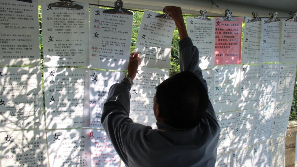 Posters list a man or woman's height, age, income, education and their hukou - registered hometown.