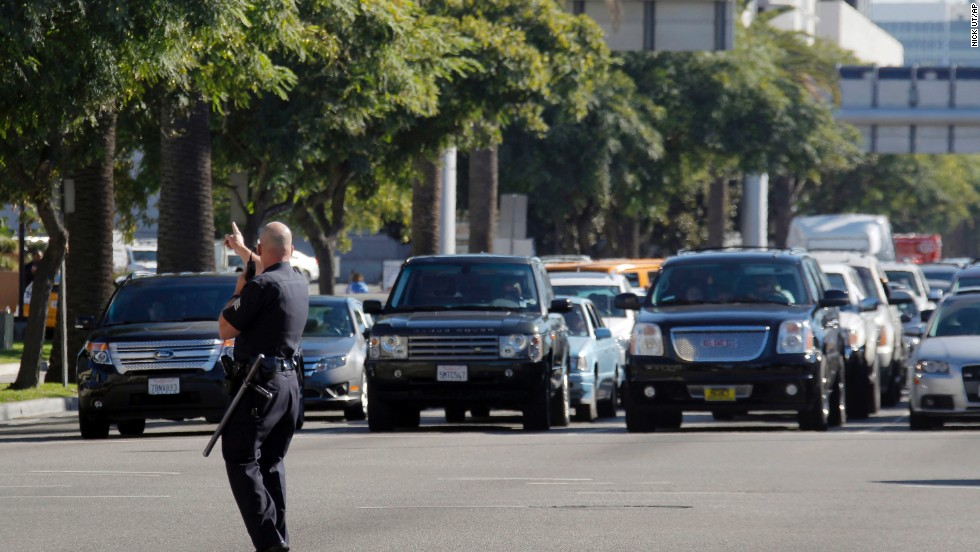 A police officer diverts traffic trying to enter the airport.