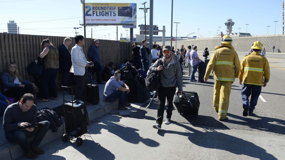 Passengers wait on the curb after leaving the airport.