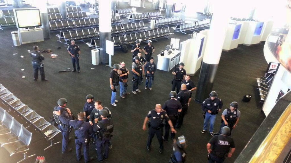 Law enforcement officers gather in Terminal 3 near the scene of the shooting.