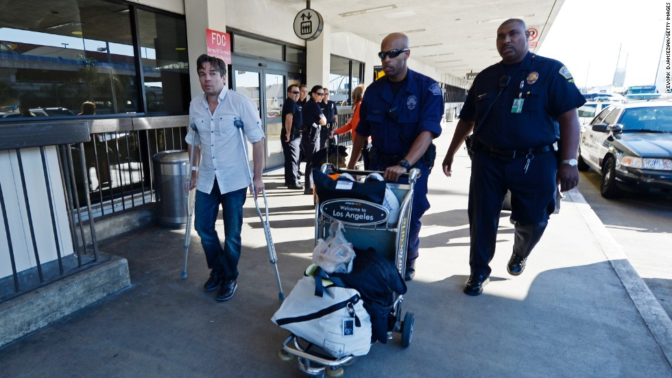 Injured traveler Bruce Reith, from Munich, Germany, is helped by two Los Angeles Airport Police officers as he makes his way on crutches to Terminal 3 for departure a day after injuring himself while escaping the shooting.