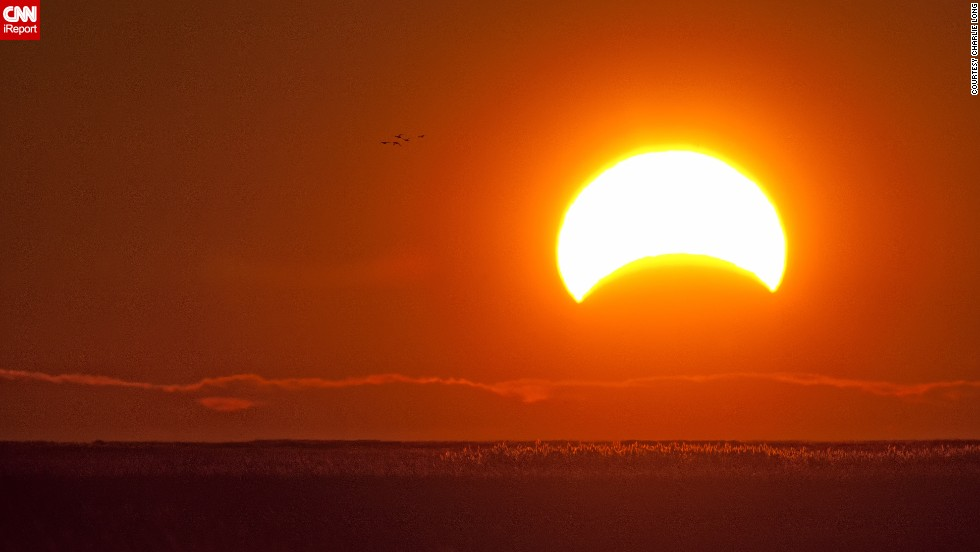 "While photographing migrating waterfowl at Delaware's Bombay Hook National Wildlife Refuge, <a href=""http://ireport.cnn.com/docs/DOC-1056317"">Charlie Long</a> captured the eclipse early Sunday morning."