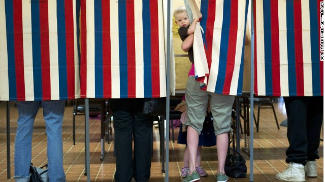 A possible future voter peeks out of the booth while his mother casts a ballot in a 2012 election in Metamora, Illinois.