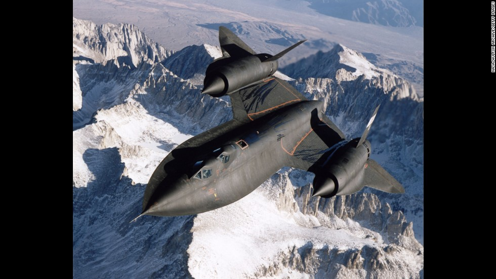 An SR-71B Blackbird flies over snow-capped mountains in 1995.