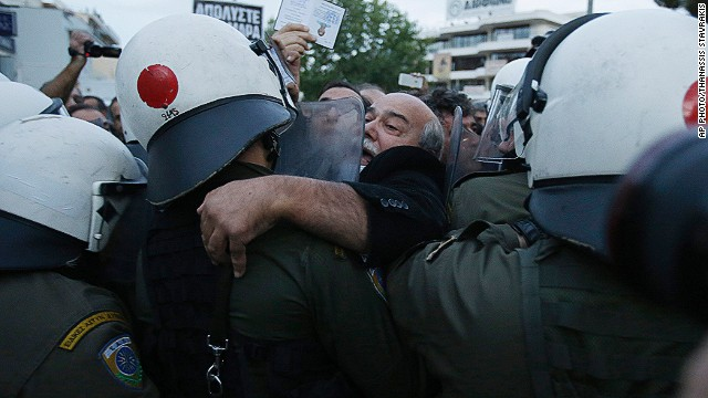Parliament Member of Syriza, main opposition party Nikos Voutsis scuffles with police as he tries to pass from a block near ERT's headquarters in the northern Athens suburb of Agia Paraskevi, Greece early Thursday, Nov. 7, 2013.