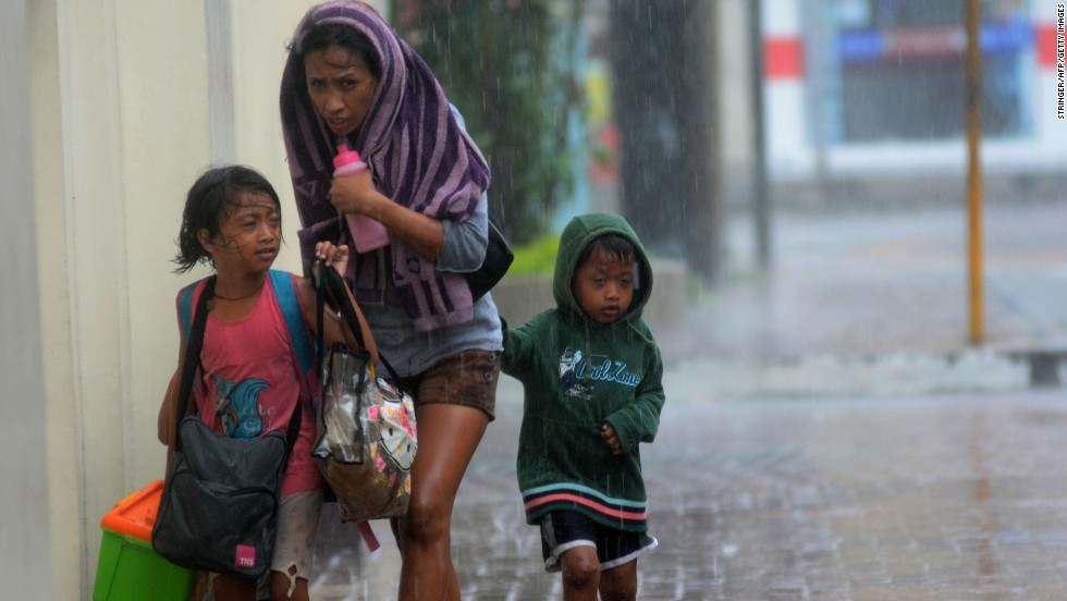 A woman and her children head for an evacuation center November 8 amid strong winds in Cebu City, Philippines.