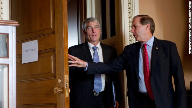 Sen. Mark Udall, D-Colo., and his cousin Sen. Tom Udall, D-N.M., attend a weekly Senate policy luncheon in Washington, D.C.