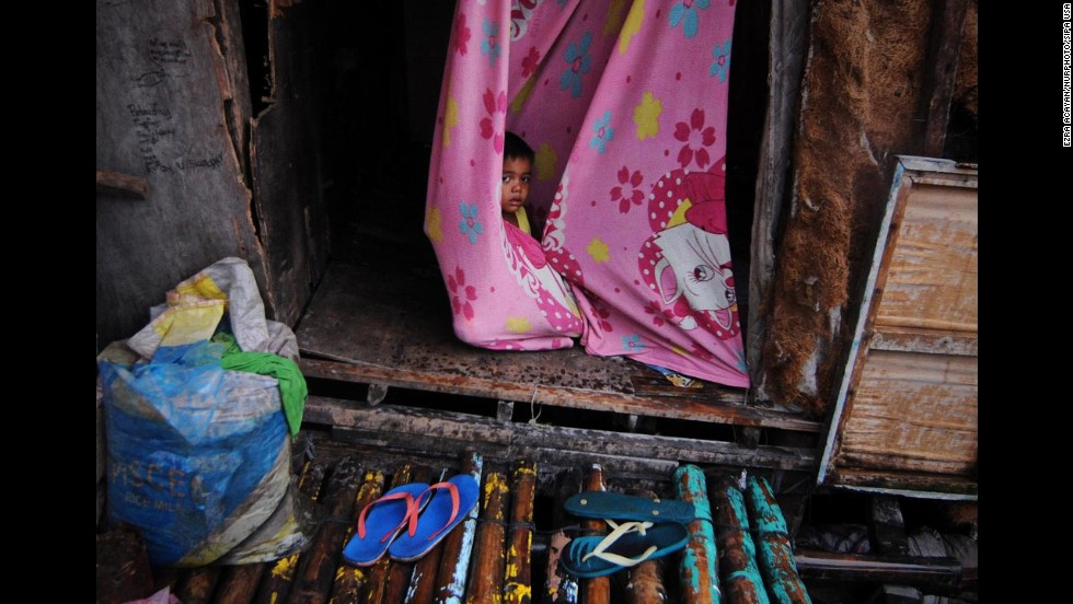 A child wraps himself in a blanket inside a makeshift house along a Bacoor fishing village.