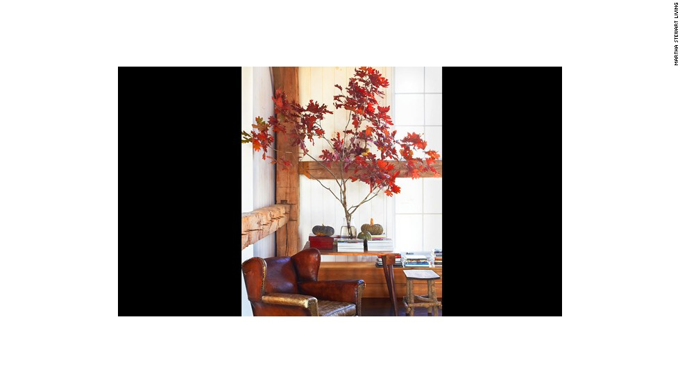 Blazing red tree branches and greenish gourds bring the autumn indoors.