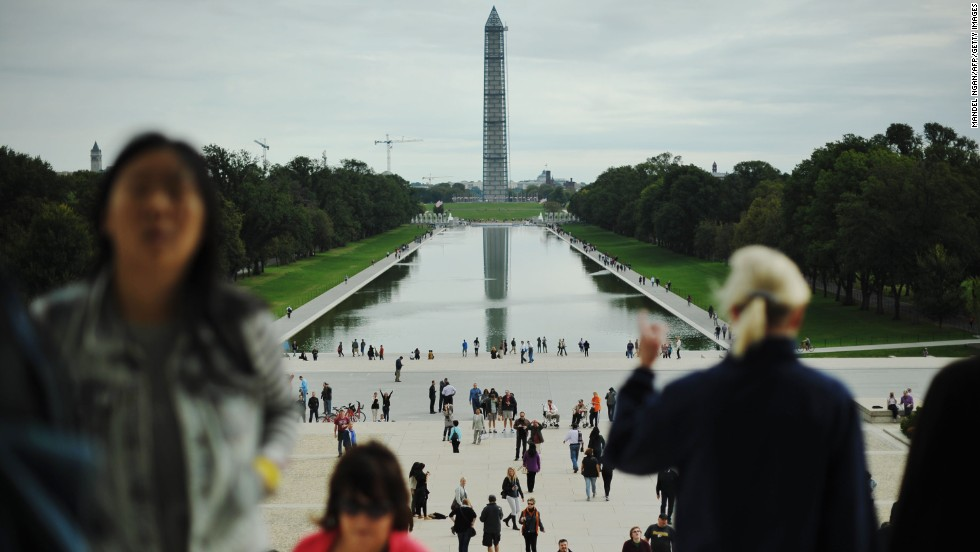 The Washington Monument stands covered in scaffolding as people visit the Lincoln Memorial in October.
