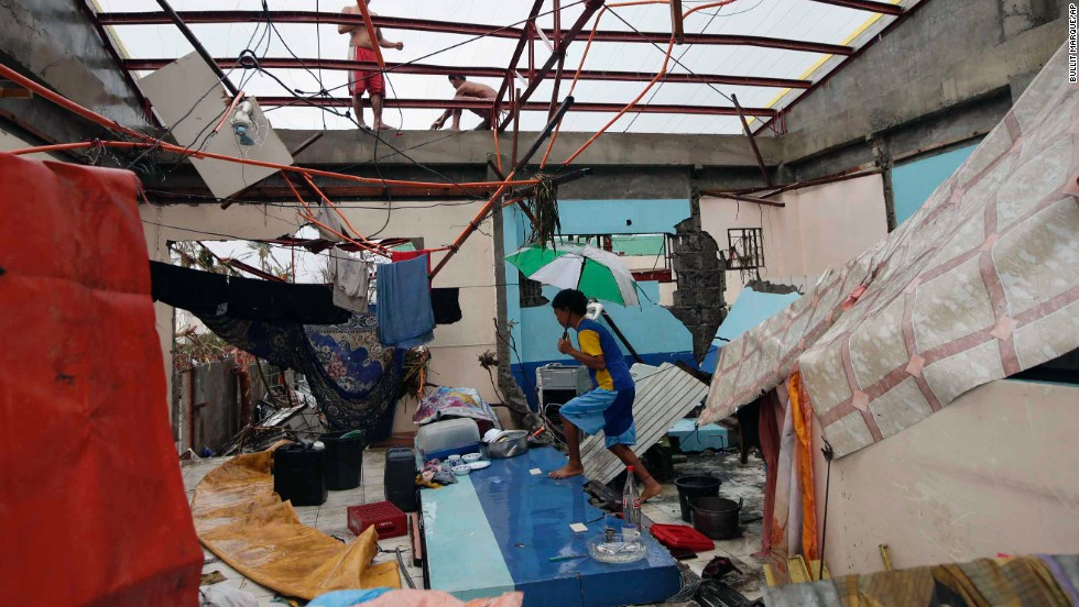 A young Tacloban resident walks inside a damaged home on November 10.