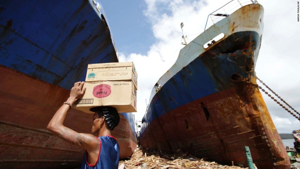 A Tacloban resident carries boxes of milk November 10 as he passes by ships washed ashore by the powerful storm.
