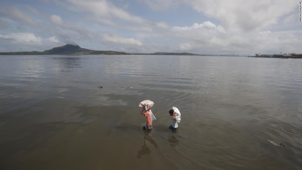 Residents carry relief goods along the bay in Tacloban on November 10.