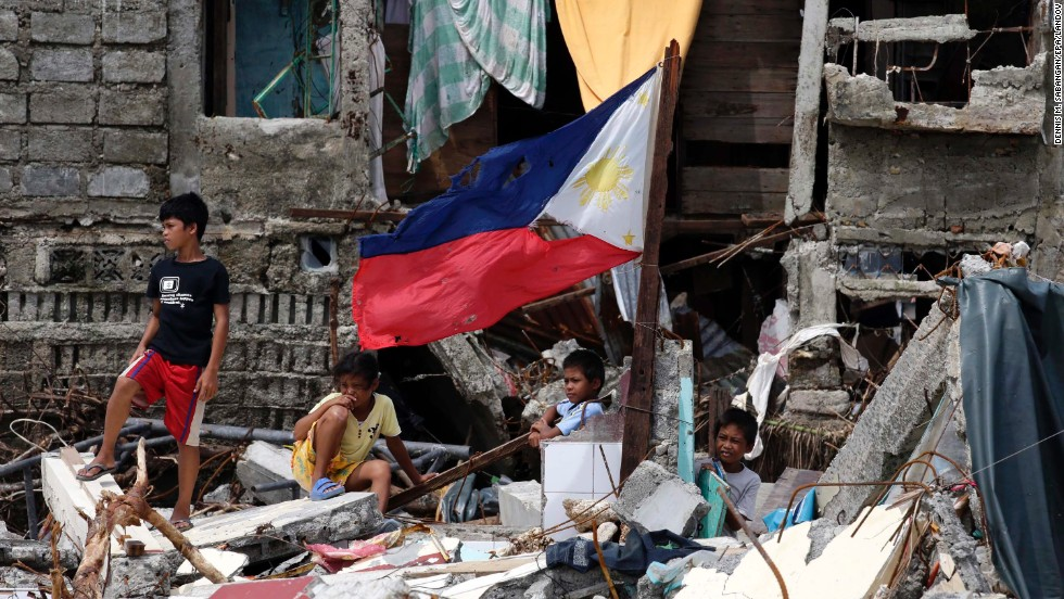 Children stand on rubble in the storm-ravaged town of Hernani, Philippines, on Monday, November 11.