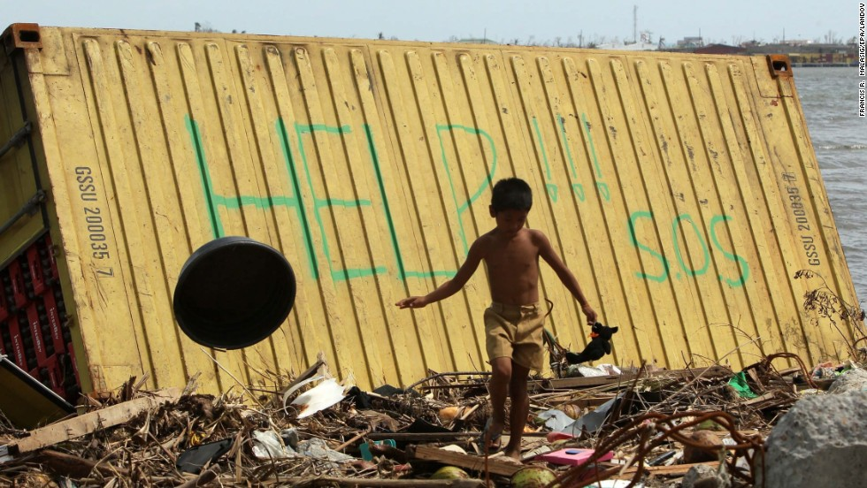 A boy in Tacloban walks near a container appealing for help.