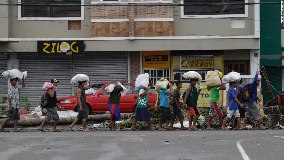 People carry sacks of goods November 12 in Tacloban.