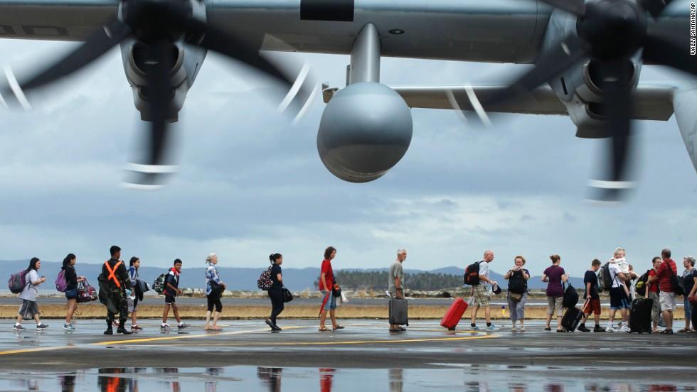 People board a U.S. military plane to evacuate Tacloban on November 12.