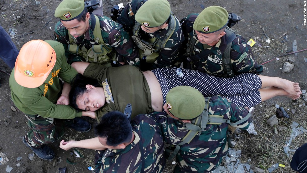 Soldiers help a woman after she collapsed November 13 while waiting in line to board a military plane at Tacloban's airport.