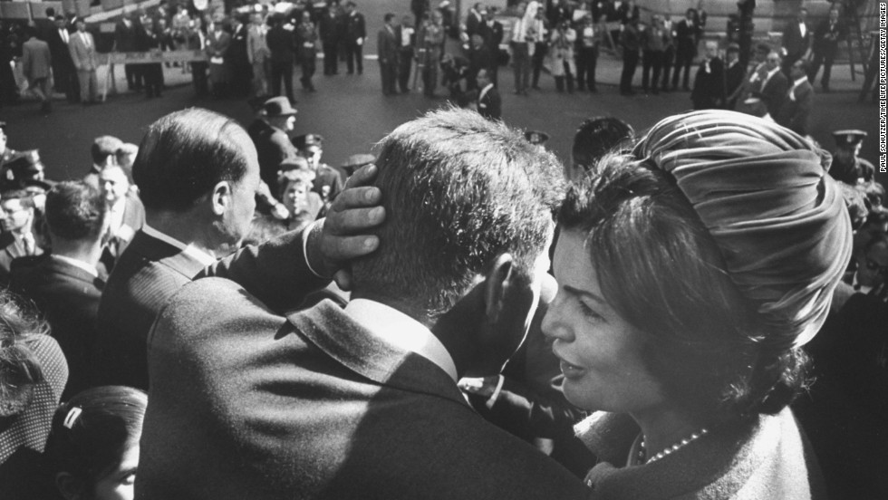 Kennedy, campaigning for president, listens to the whispers of his wife in 1960.