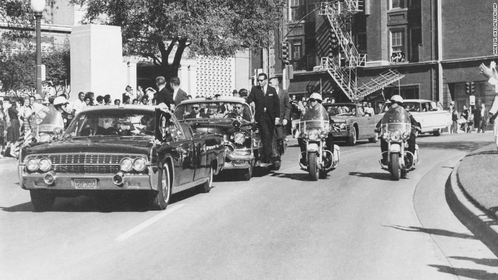 Seen through the limousine's windshield as it proceeds along Elm Street past the Texas School Book Depository, Kennedy appears to raise his hand toward his head after being shot. The first lady holds Kennedy's forearm in an effort to aid him.