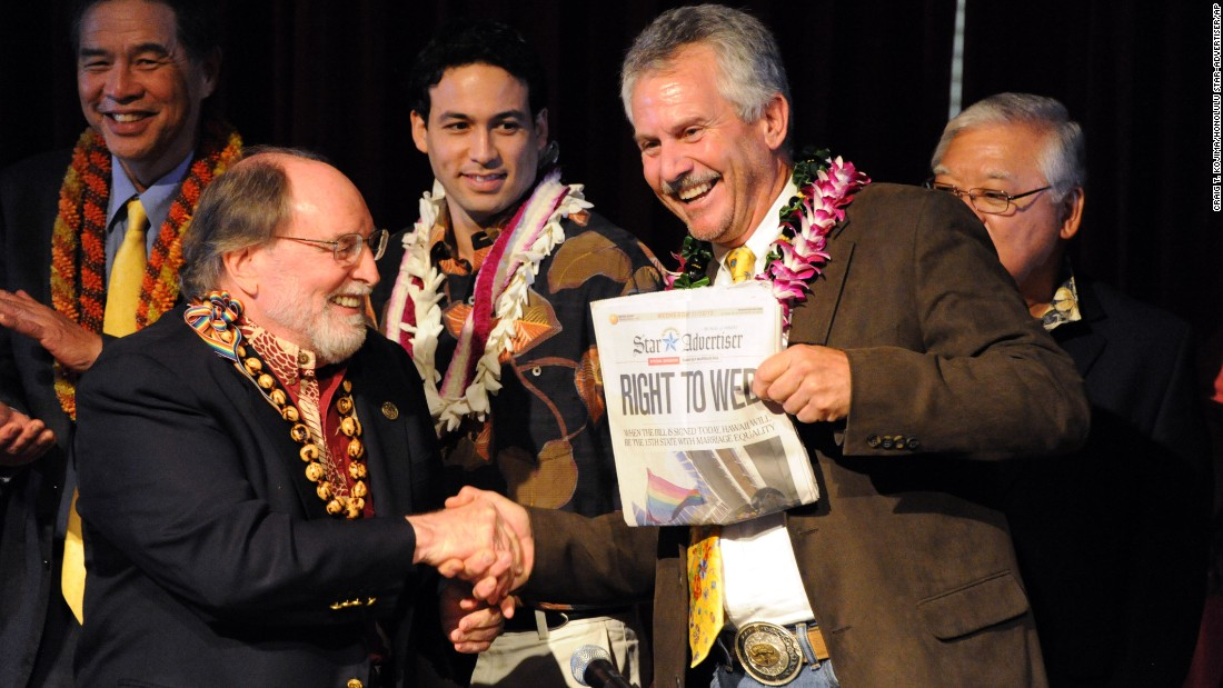 On November 13, 2013, Hawaii Gov. Neil Abercrombie, left, and former state Sen. Avery Chumbley celebrate with a copy of the Honolulu Star-Advertiser after Abercrombie signed a bill legalizing same-sex marriage in the state.