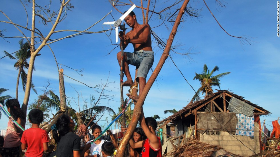 A family, desperate to charge their mobile phones to search for family and friends, tries to use a ceiling fan to generate electricity November 13 in the Philippine province of Cebu.
