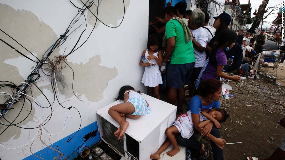 Tacloban residents ask for water while waiting to get a free pass to board a U.S. plane Tuesday, November 12.