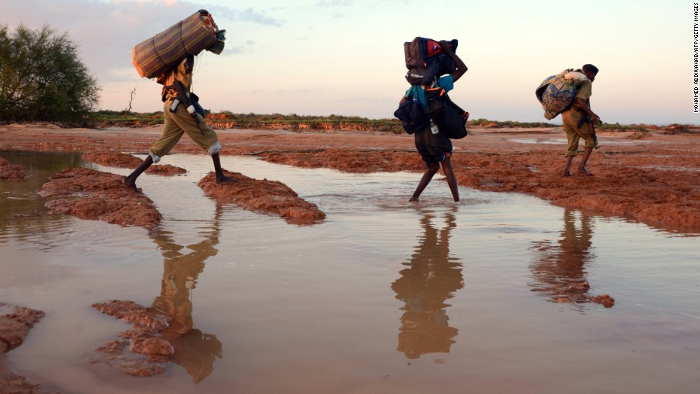 People walk with their belongings in the area around Sinujiif as they evacuate on November 14, 2013 after a ferocious storm and days of heavy floods in Somalia's northeastern Puntland region. Somalia has ranked in the top 10 in Maplecroft's political risk index for the past six years.
