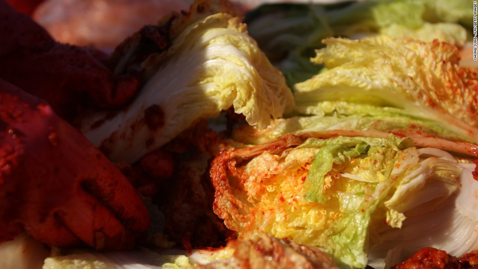 Making kimchi is a labor-intensive process involving salting cabbage, mixing in pureed chili mixture and adding fish sauce and shrimp sauce. Rubber gloves are necessary to prevent chili burn.