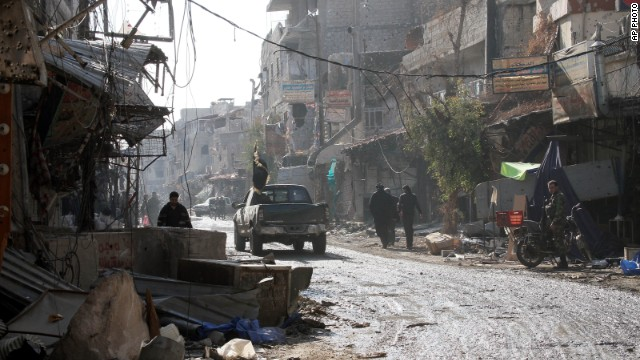 People walk on a street between destroyed buildings in the town of Hejeira in the countryside of Damascus on November 13.