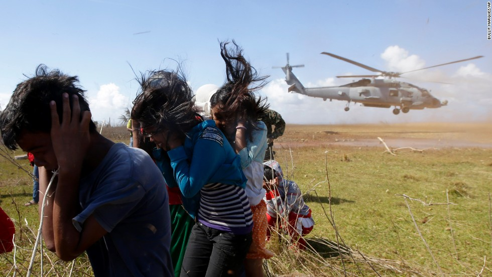 Trapped residents protect themselves from dust as a U.S. Navy helicopter takes off Saturday, November 16, on the Philippines' Manicani Island.
