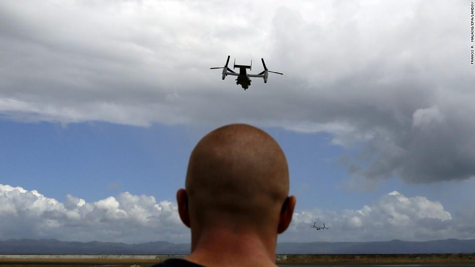 A U.S. aircraft flies above the Tacloban airport as a U.S. Marine watches November 16.