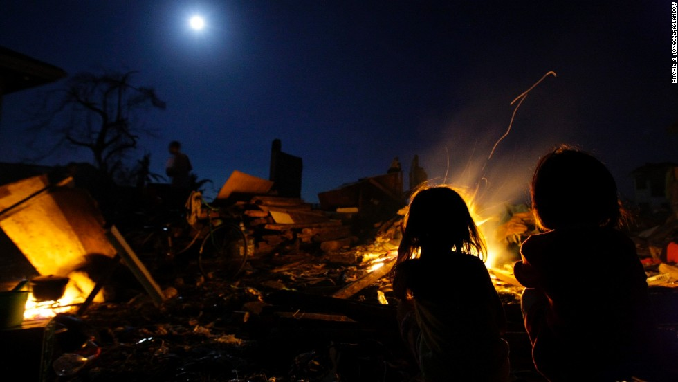 Young girls stare at the full moon outside a makeshift shelter in Tacloban on Saturday, November 16.