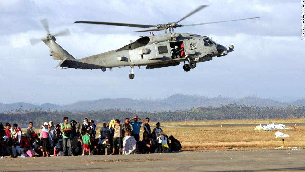 Evacuees wait to board military aircraft while a U.S. Navy helicopter takes off November 16 in Tacloban.
