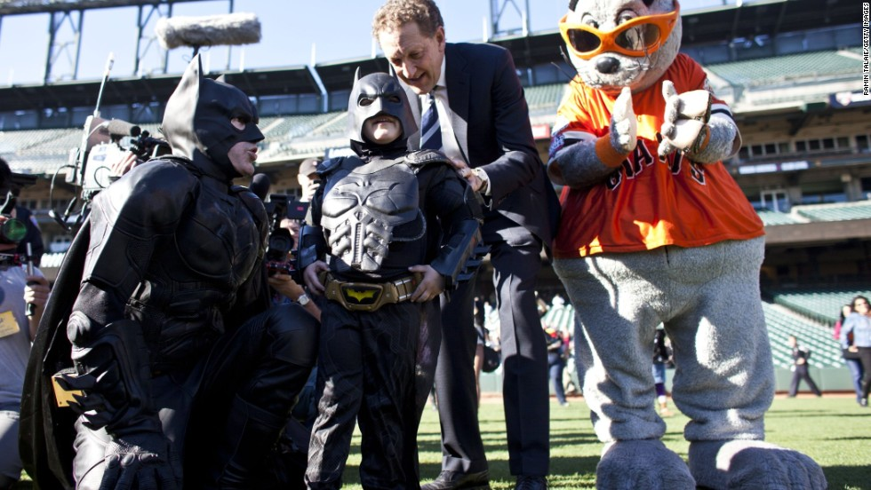 Larry Baer, CEO of the San Francisco Giants, and the team's mascot Lou Seal escort Miles and Batman at AT&T Park.