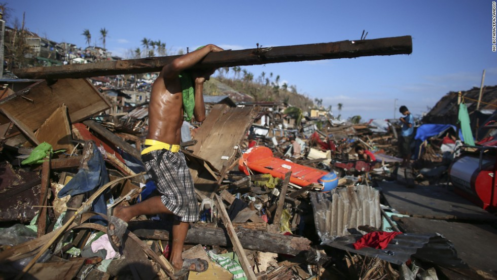 A man carries a piece of wood from the debris in Tacloban on November 17.