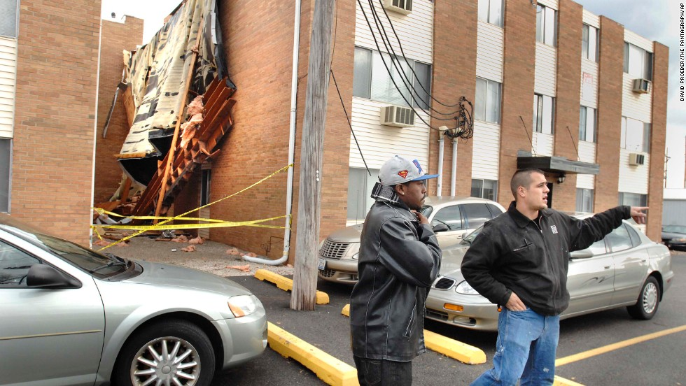 """An apartment manager warns Illinois State University students to stay back from a roof that blew off """"The U"""" student apartments in Normal, Illinois, on November 17."""