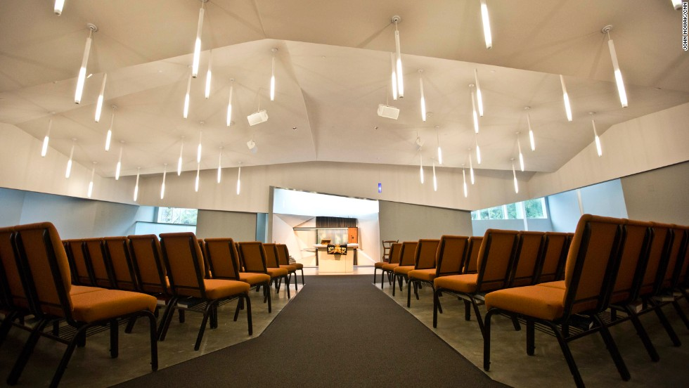 The sanctuary features modern lighting and asymmetrical walls and ceilings. It was engineered to maximize acoustic performance. Because they were on a tight budget, they kept the same chairs the congregation relied on before it had its own space.