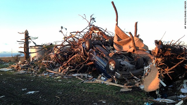 An overturned car rests atop tree branches and other rubble near Washington, Illinois, on Sunday.