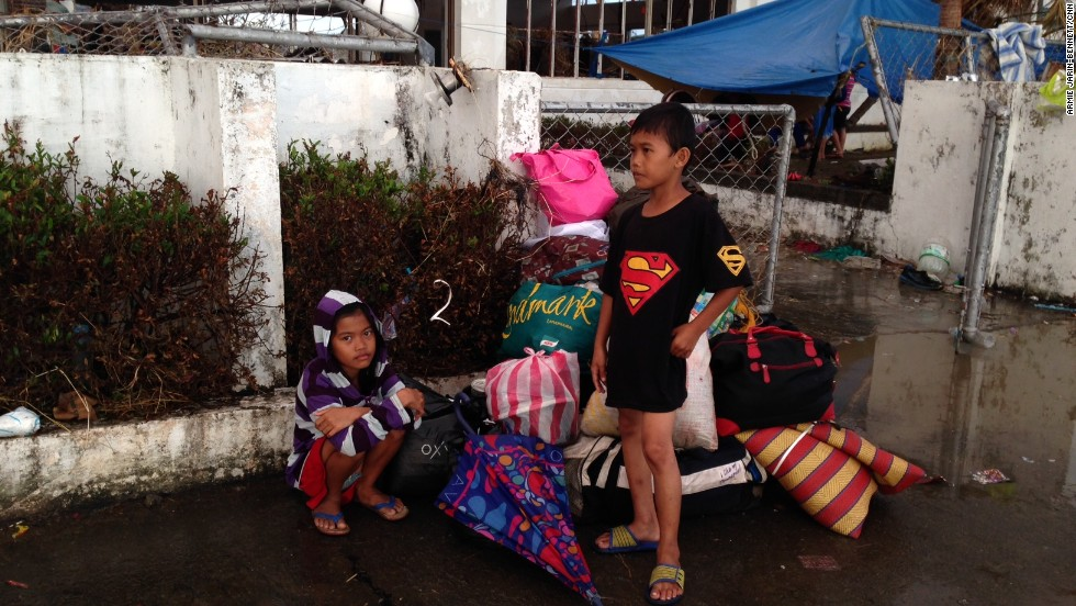 These two young boys wait patiently to get on a plane out of storm-ravaged Tacloban on November 13.